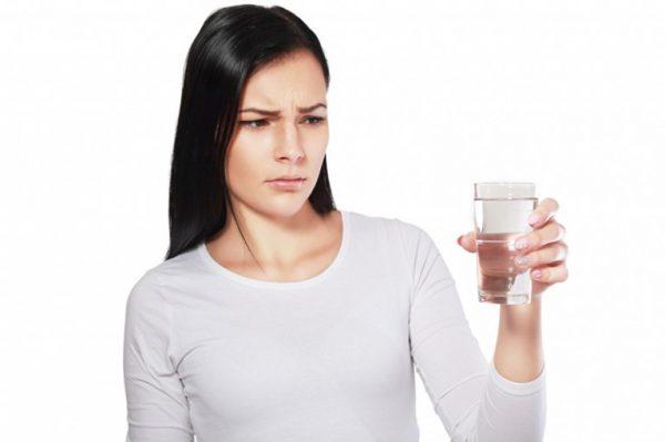 Женщина смотрит на стакан с водой