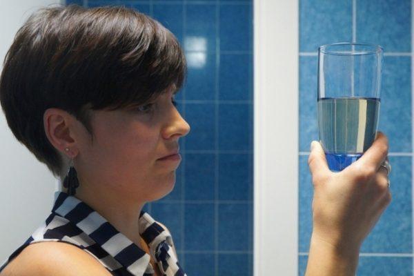 Женщина держит стакан с грязной водой