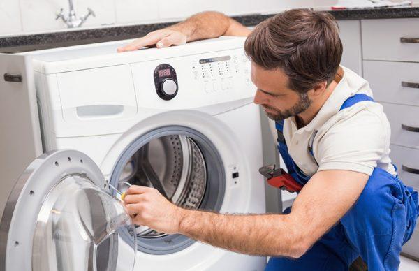 специалист чинит стиральную машину