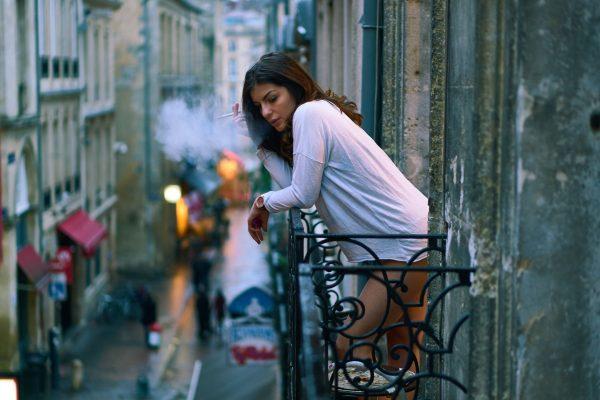 Женщина курит на балконе